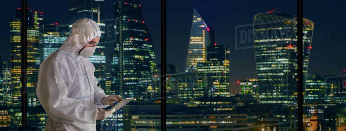 Scientist in clean suit with digital tablet working late city window Royalty-free stock photo