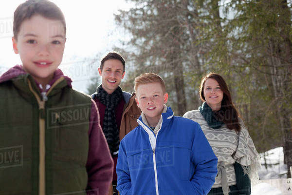 Portrait of smiling family in snowy woods Royalty-free stock photo