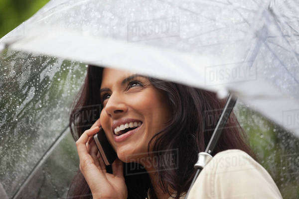Happy woman talking on cell phone under umbrella in rain Royalty-free stock photo