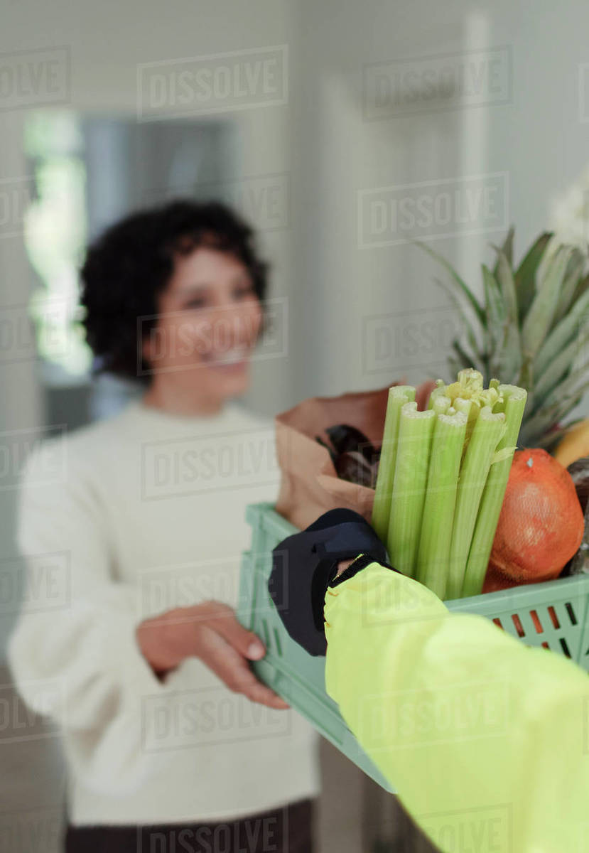 Woman receiving grocery delivery from courier Royalty-free stock photo