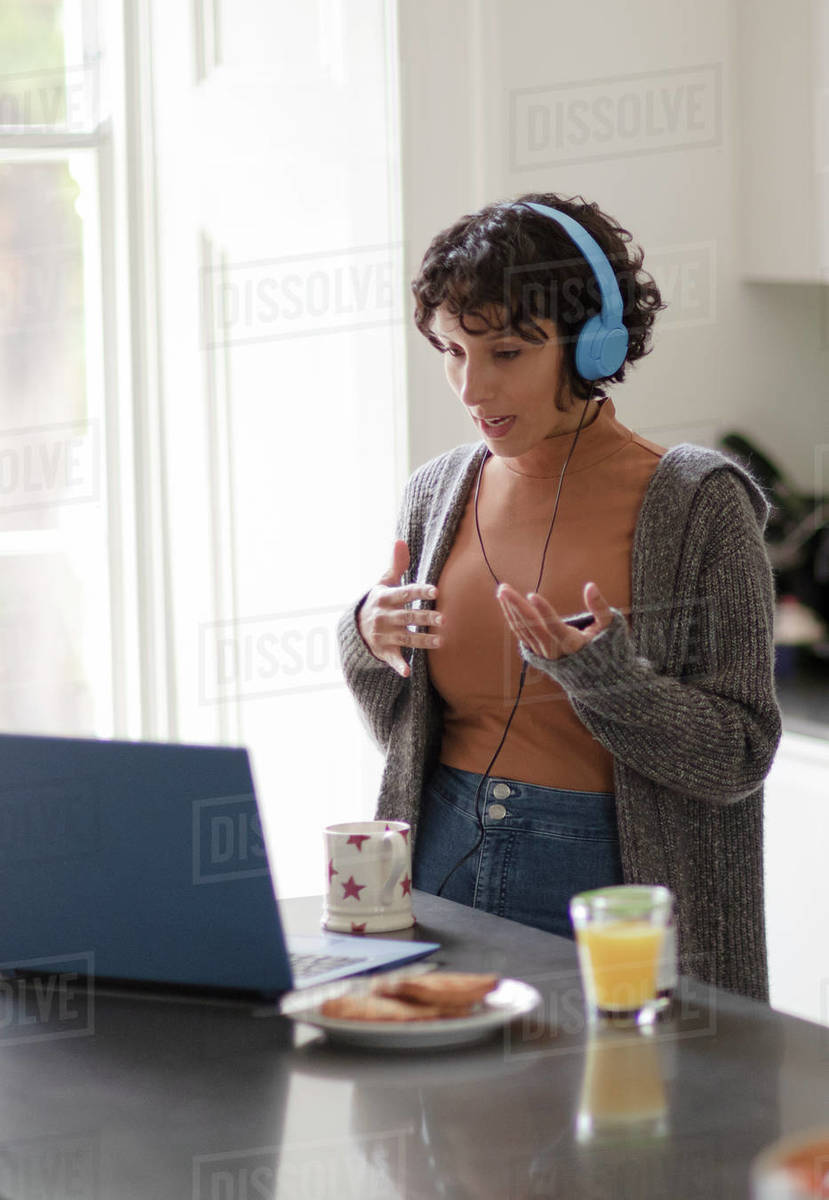 Woman with headphones on video call working from home at laptop Royalty-free stock photo