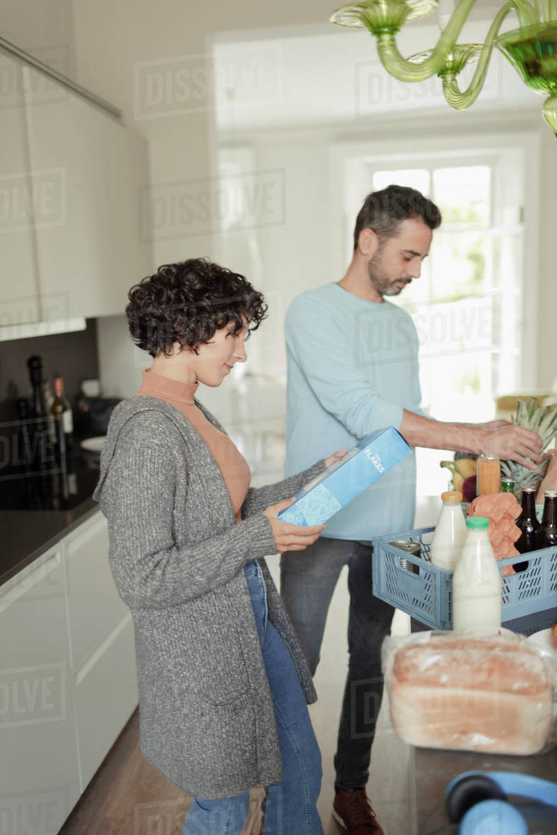 Couple unloading groceries in kitchen Royalty-free stock photo