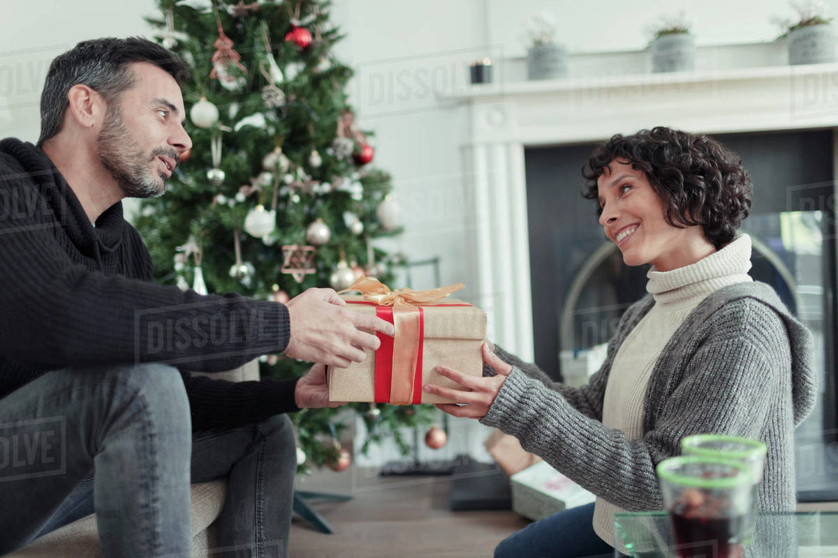 Husband giving Christmas gift to wife in living room with tree Royalty-free stock photo
