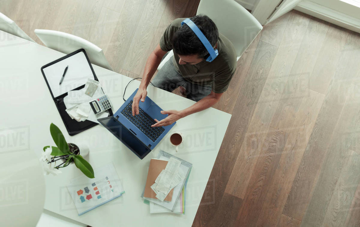 Man with headphones working from home at laptop on dining table Royalty-free stock photo