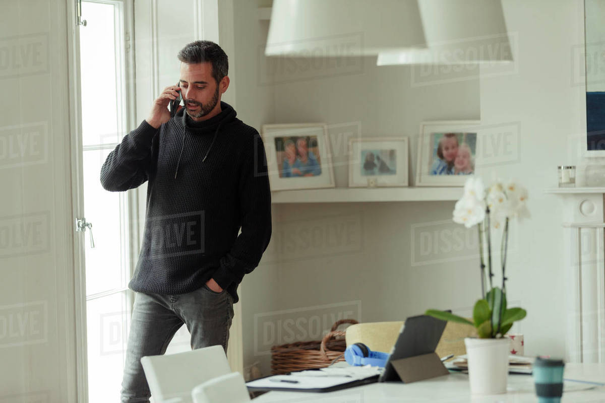 Man working from home talking on smart phone at window Royalty-free stock photo