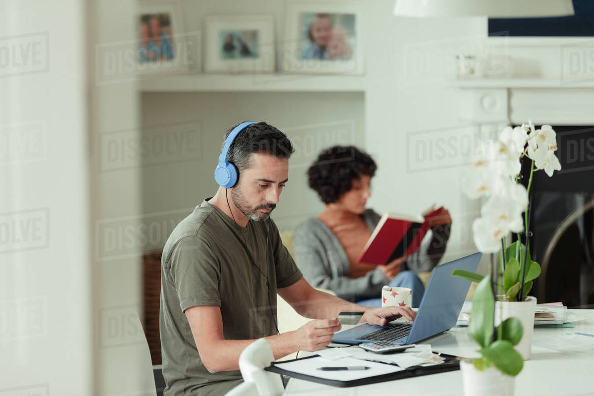 Man with headphones and credit card paying bills at laptop Royalty-free stock photo