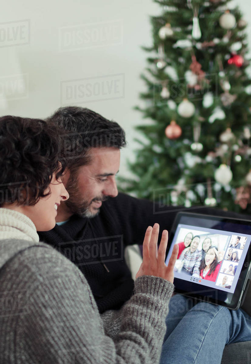 Happy couple video chatting with family on digital tablet at Christmas Royalty-free stock photo