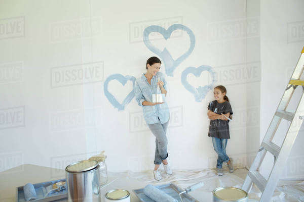 Mother and daughter painting blue hearts on wall Royalty-free stock photo