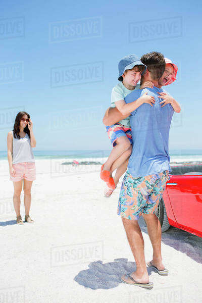 Father hugging children on beach Royalty-free stock photo