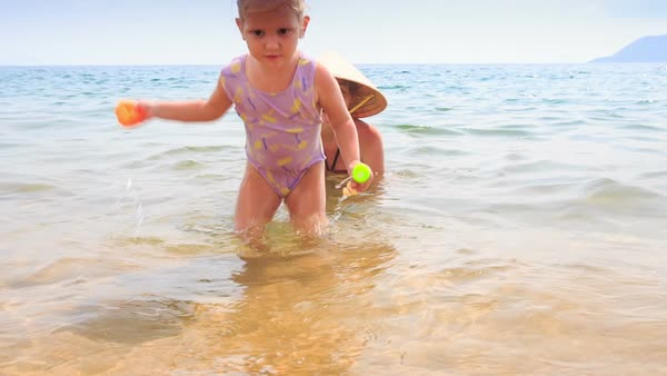 6e0df3fcb5 Close-up mother in hat and bikini let little daughter with pigtail go to  sand