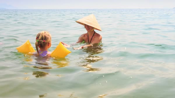 881d7c3cc0 Close-up little girl in yellow safety armbands swims to mother in hat in  azure