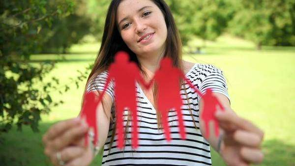 Young woman with red family paper dolls at the park Royalty-free stock video