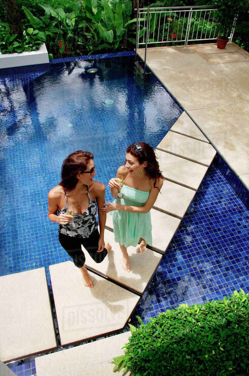 Two women standing next to swimming pool, talking stock photo