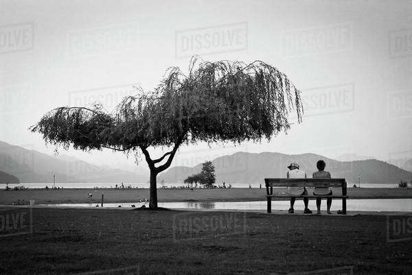 Two people sitting on a bench, Harrison Hot Springs, British Columbia Royalty-free stock photo