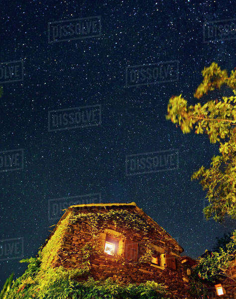 An ivy covered house under a star filled night sky Royalty-free stock photo