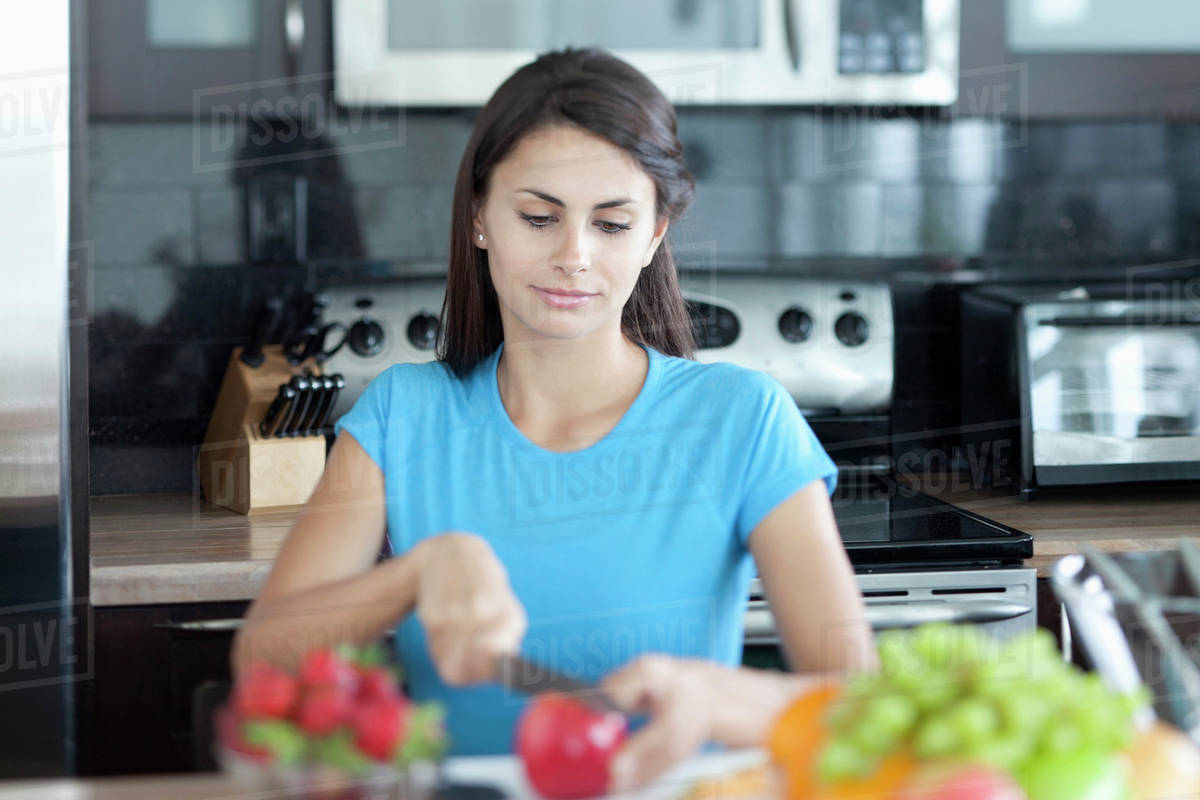Woman slicing apple in kitchen - Stock Photo - Dissolve