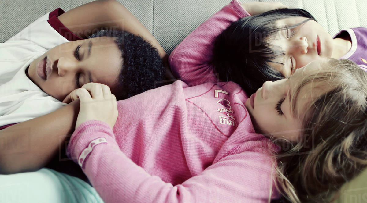 Three kids comfortably napping together on a sofa Royalty-free stock photo