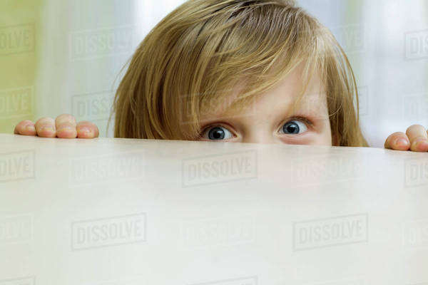 A mischievous girl peeking over the top of a table Royalty-free stock photo