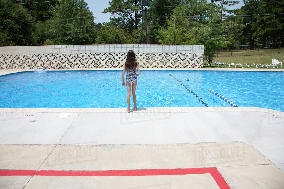 A girl standing at the edge of a swimming pool - Stock Photo - Dissolve