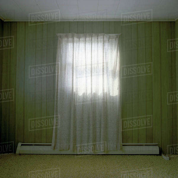 A room bare of furniture with a single curtained window Royalty-free stock photo
