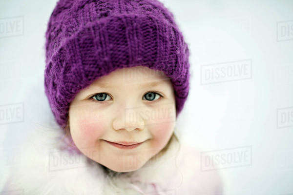 A young smiling girl wearing a knit cap, outdoors in winter Royalty-free stock photo