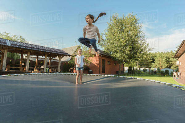 Girl with sister jumping on trampoline in yard Royalty-free stock photo