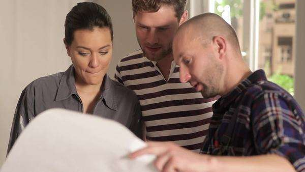 Close-up, Rack Focus, Handheld of young couple and a contractor reviewing blueprints Royalty-free stock video
