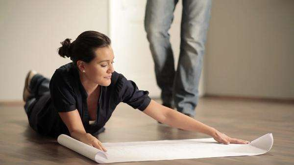 Close-up of couple lying on the floor looking at blueprints Royalty-free stock video