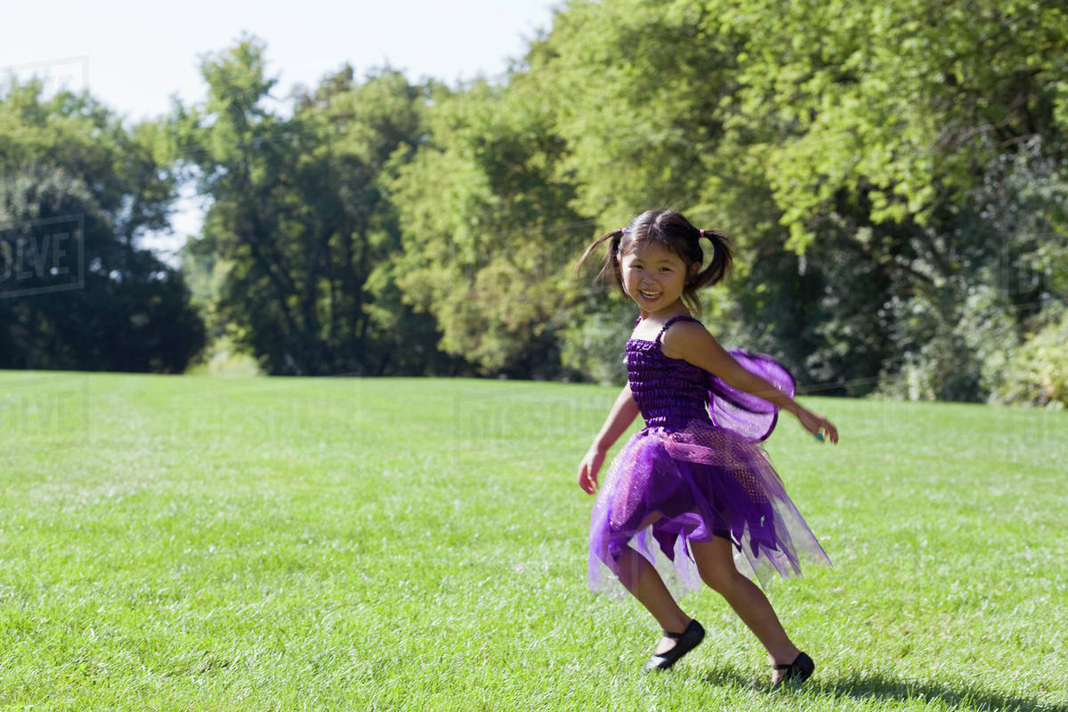 A young girl in a fairy costume running in a back yard Royalty-free stock photo