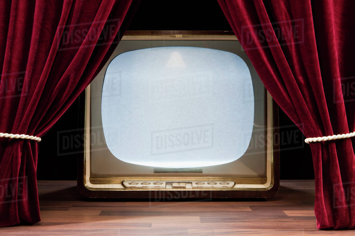 an old fashioned television behind red theatre curtains stock