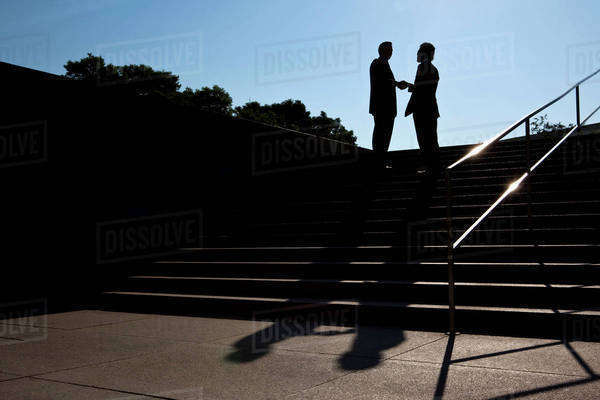 Two businessmen shaking hands, outdoors, silhouette Royalty-free stock photo