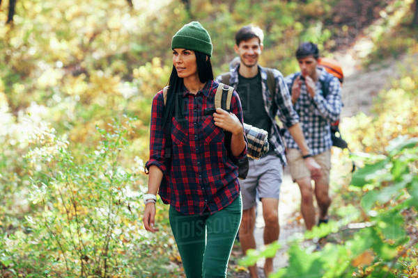 Young woman hiking with friends in forest Royalty-free stock photo