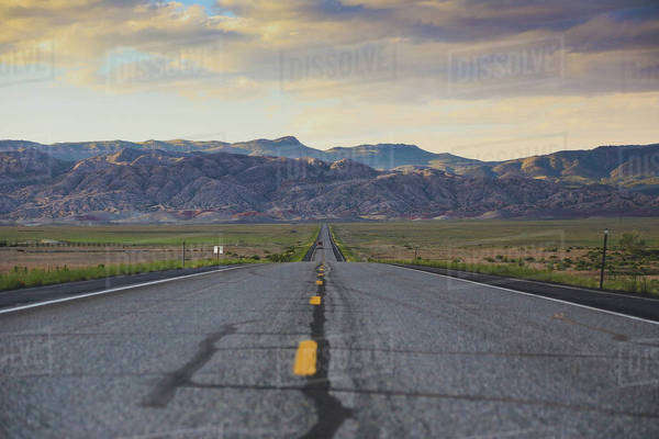 Road leading towards rocky mountains against cloudy sky Royalty-free stock photo