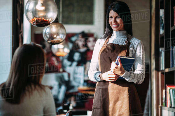 Happy waitress talking to female customer in coffee shop Royalty-free stock photo