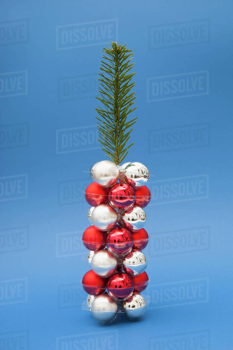 Christmas Tree Made Of Twig And Ornaments Against Blue Background
