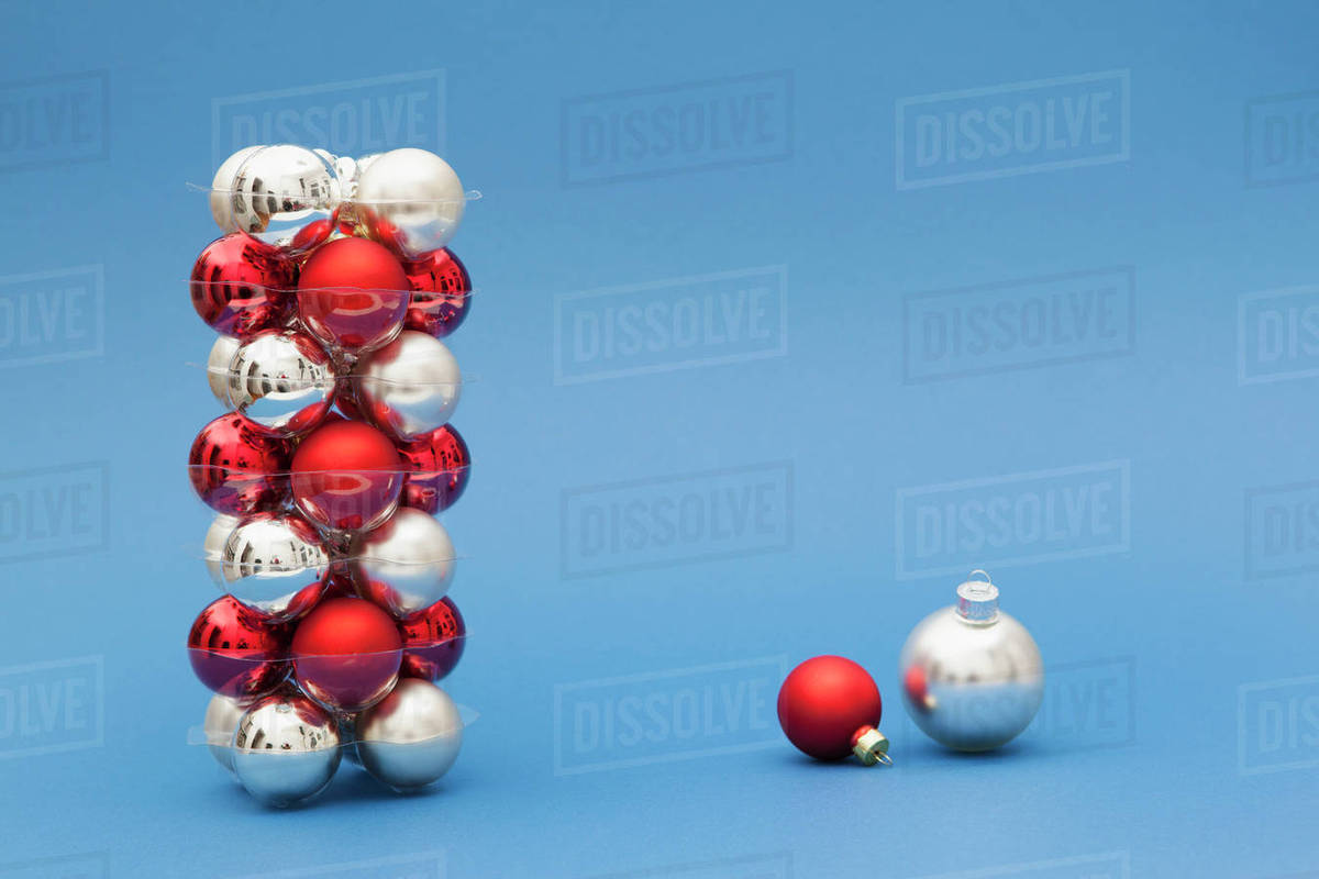 stack of red and silver colored christmas ornaments on blue background - Red And Silver Christmas Ornaments