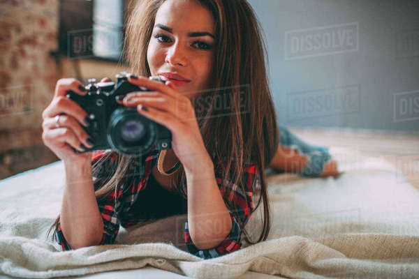 Portrait of young woman holding SLR camera while lying on bed at home Royalty-free stock photo