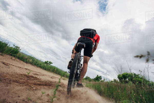 Low angle view of man riding mountain bike on dirt road against cloudy sky Royalty-free stock photo