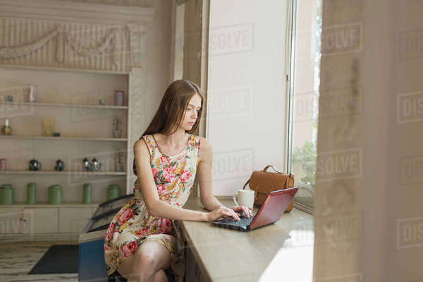 Young woman using laptop while sitting by window at cafe Royalty-free stock photo