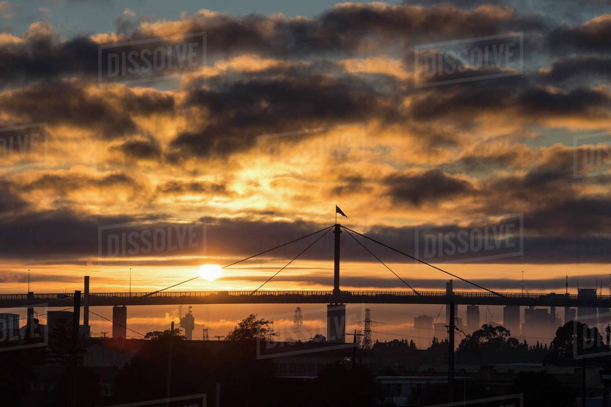 e16a8a93d9 Bridge and skyline against cloudy sky during sunset