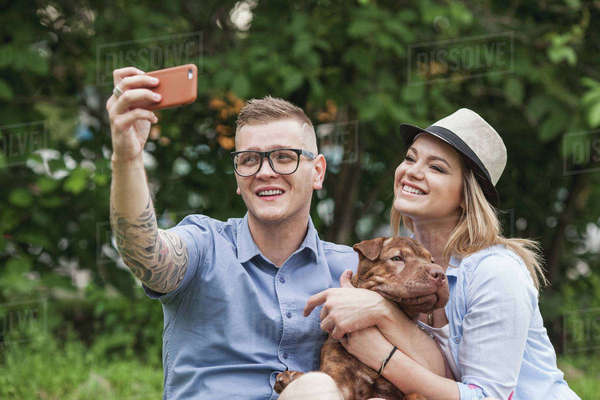 A couple with their Shar-pei/Staffordshire Terrier dog at the park taking a selfie Royalty-free stock photo