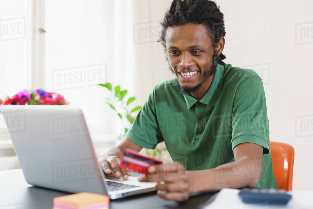 Happy man shopping online through laptop at home Royalty-free stock photo