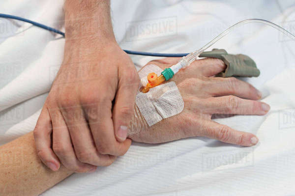 Close-up of man holding hand of a woman with IV drip at hospital Royalty-free stock photo