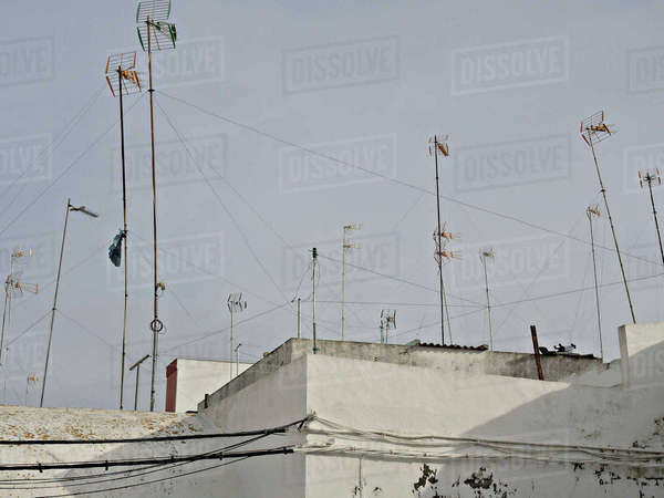Low angle view of television aerials on building against clear sky Royalty-free stock photo