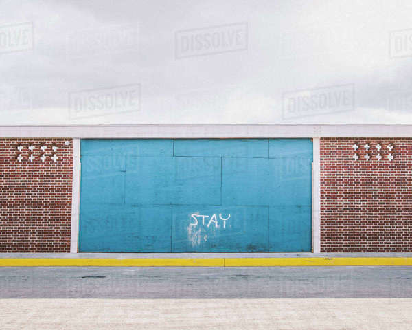 Text on blue wall against cloudy sky Royalty-free stock photo