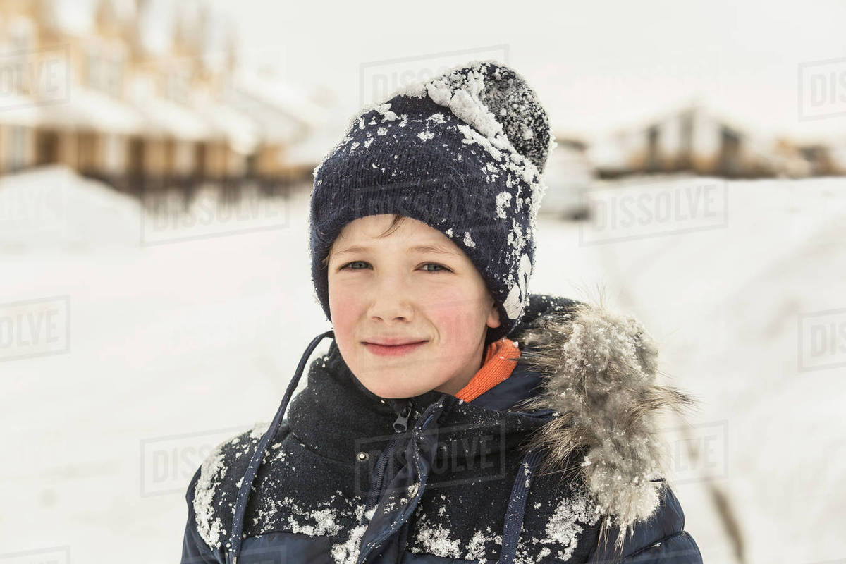 db56409238 Portrait of confident boy in winter wear covered with snow - Stock ...