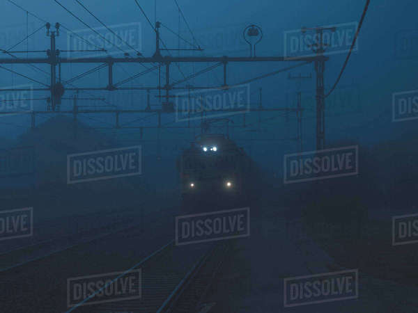 Train on railroad tracks in foggy weather Royalty-free stock photo