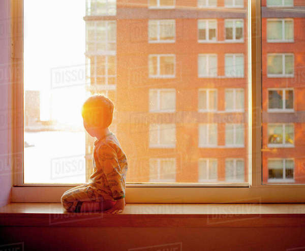 Side view of boy looking out while kneeling on window sill at home Royalty-free stock photo
