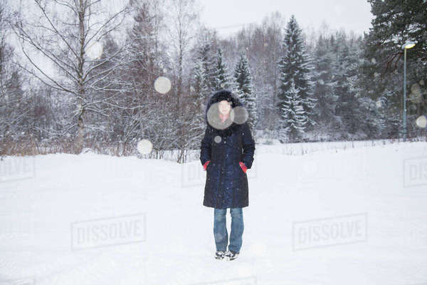 Full length portrait of mid adult woman standing on snow covered field Royalty-free stock photo