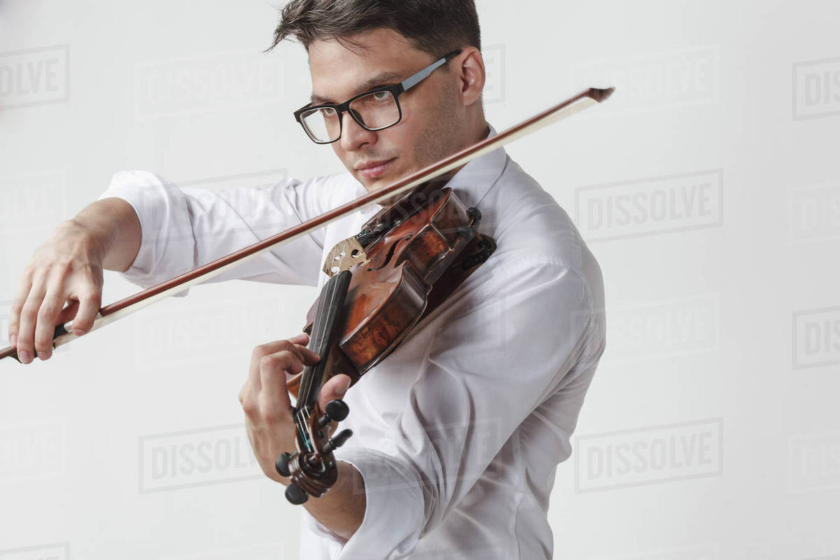 Confident young man playing violin against white background - Stock Photo -  Dissolve